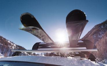 Skidor fastspända på ett biltak